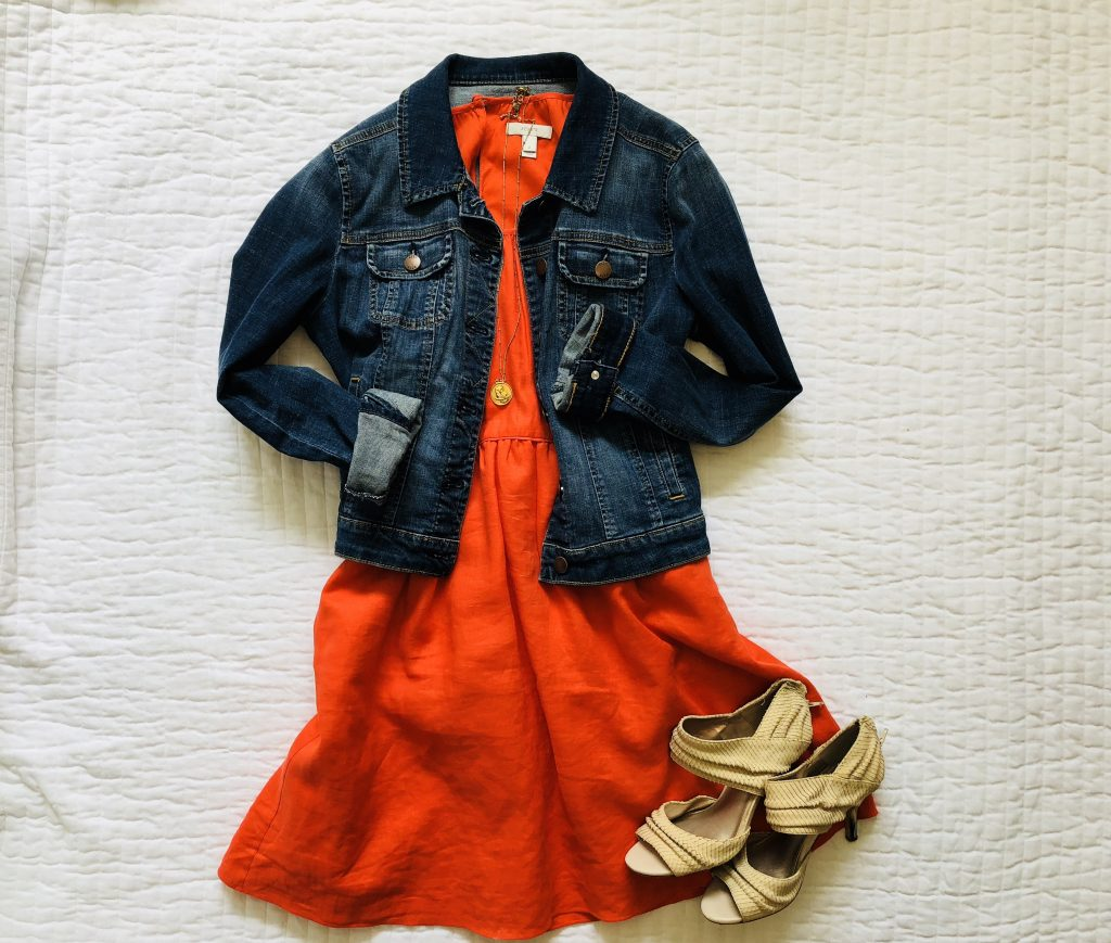Denim jacket styled with orange sundress and sandals