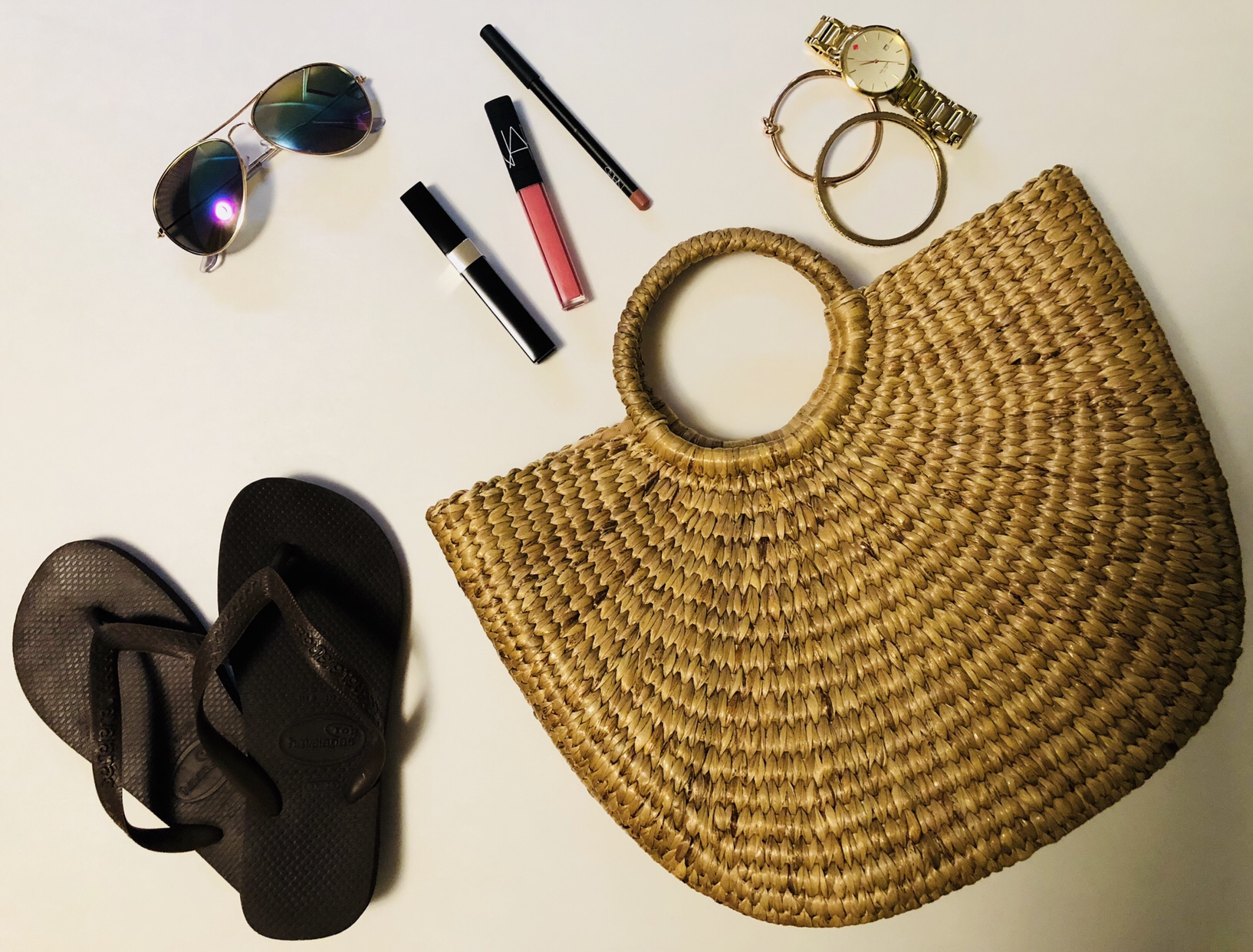 straw handbag flat lay with accessories