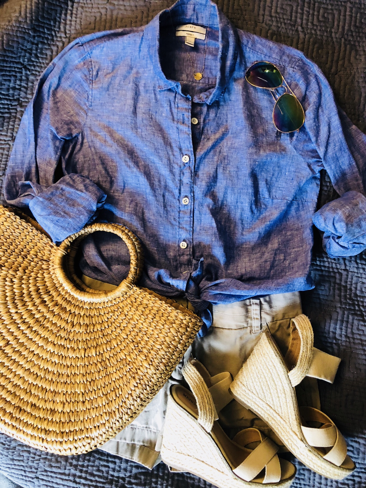 flat lay with straw bag, linen top and khaki shorts