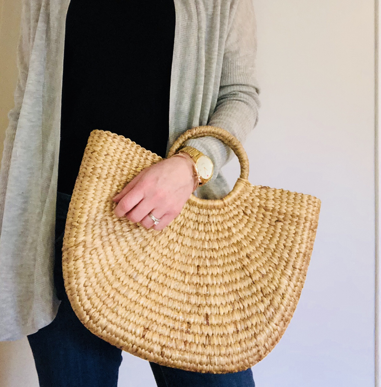 straw handbag with grey sweater, black top and jeans